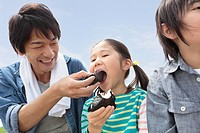 Father and children eating rice ball