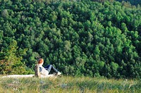 Girl sitting on a high hill near the steep in Russian National Park 'Samara Luka'