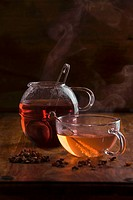 Cup of yellow fruit tea and pot of red fruit tea