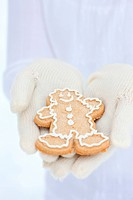 Hands with winter gloves holding Christmas gingerbread cookie