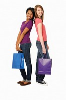 Two teenage girls with shopping bags, smiling at viewer