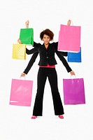 Young woman as shopping goddess, holding many bags in her multiple arms  Model is of mixed ethnic background African and Caucasian