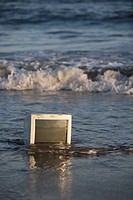 Discarded obsolete broken computer monitor left abandon on public beach