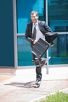 Businessman in suit inline skating (thumbnail)
