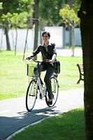 Woman in suit riding bike