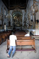 Brazil. Salvador, Bahia. Man praying inside the Igreja de Bonfin Church