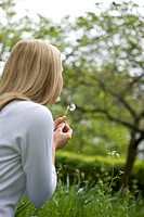 A young woman blowing a dandelion clock