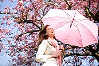 A young woman holding an umbrella, in springtime (thumbnail)