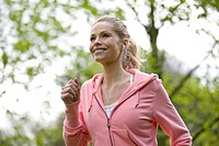 A mid adult woman jogging in the park, wearing headphones (thumbnail)