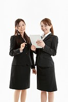 Two businesswomen holding tablet