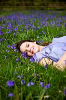 A young woman lying amongst bluebells, smiling