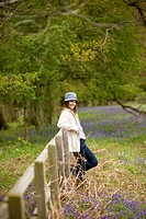 A young woman leaning against a fence in the countryside, smiling