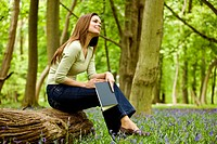 A young woman sitting on a log, holding a book