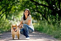 A young woman and her dog outdoors in summertime