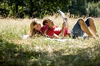 A young couple lying in the grass, reading newspapers