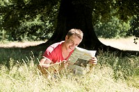 A young man sitting on the grass, reading a newspaper (thumbnail)