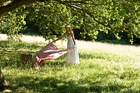 A young woman laying a picnic blanket on the grass