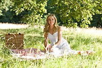 A young woman sitting on a picnic blanket