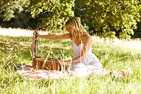 A young woman opening a picnic basket