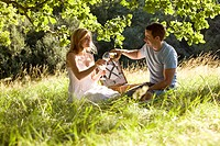 A young couple having a picnic, man pouring sparkling wine