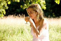 A young woman sitting on the grass, drinking a glass of orange juice