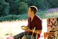 A young man having a picnic, laughing
