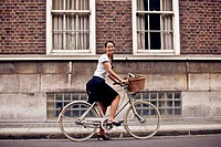 A young woman on a bicycle, smiling