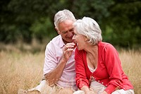 A senior man feeding his wife a strawberry, outdoors