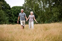 A senior couple walking through a field, holding hands