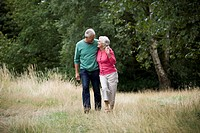 A senior couple walking in the countryside, embracing