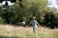 A young boy playing football in a field