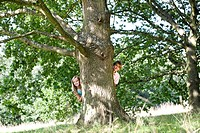 A young boy and girl hiding behind a tree
