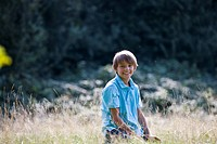 A young boy sitting in long grass, smiling