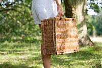 A woman carrying a picnic basket, close_up
