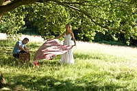 A young couple laying a picnic blanket on the grass