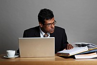 Indian man working at desk with laptop