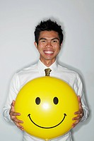 young man holding a big smiley face balloon and smiling
