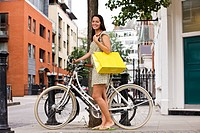 A young woman standing next to her bicycle, carrying a shopping bag