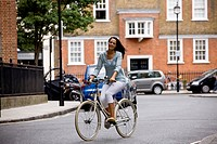 A young woman riding her bicycle in the street