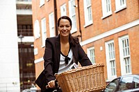 A businesswoman riding a bicycle, smiling