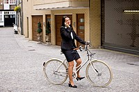A businesswoman on her bicycle, using her mobile phone