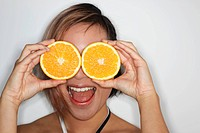 Young woman holding large orange slices over her eyes and laughing