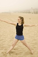 Portrait of a young woman exercising at beach.