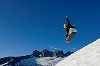 Snow boarder makes a jump on slopes in the Juneau area with Mendenhall Glacier and Towers in the background, southeast, Alaska