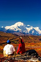 A couple hiking in Peters Hills stop to take a picture of Mt. McKinley with a cell phone, Denali State Park, Southcentral Alaska, Fall/n