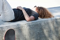 Young woman lying on wall