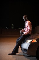 Businessman with laptop in car park at night