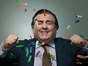 Mature businessman with ticker tape, portrait (thumbnail)