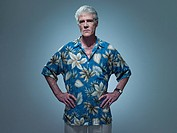Senior man wearing hawaiian shirt with hands on hips, portrait