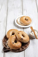 Bagel on plate with cream cheese and butter knife